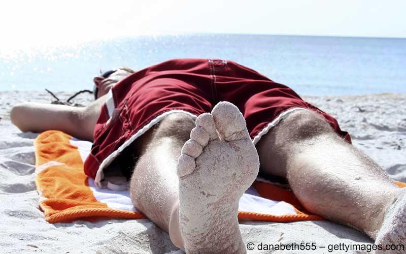 Mann liegt am Strand