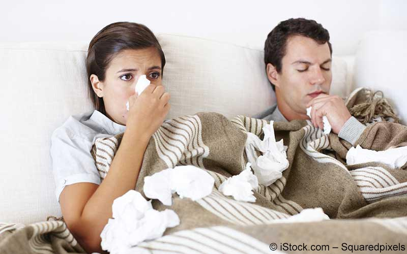 Paar liegt mit Grippe im Bett