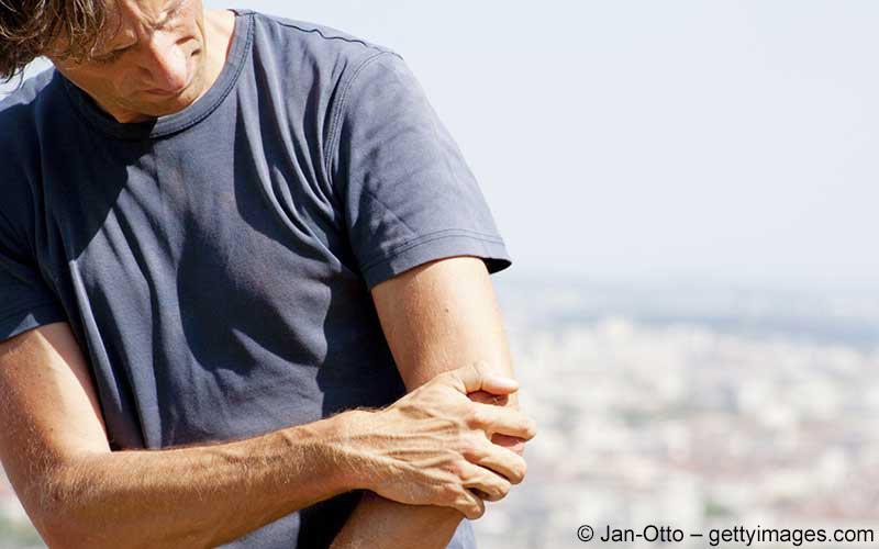 Mann hält Arm fest
