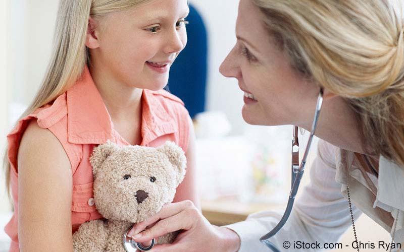 Ärztin untersucht Kind mit Teddy