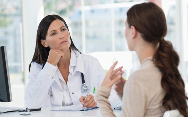 Frau spricht mit Ärztin