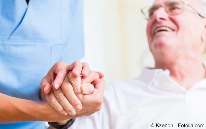 Krankenhelfer hält die Hand eines Patienten