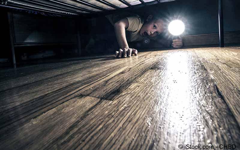 Junge schaut ängstlich unter dem Bett