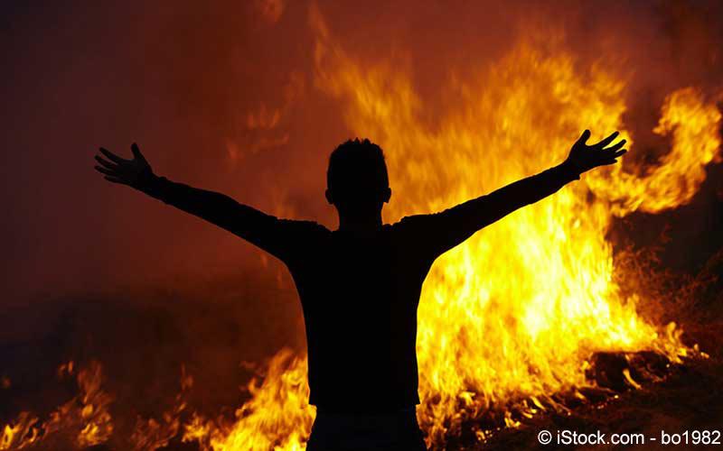 Mann steht vor Feuer